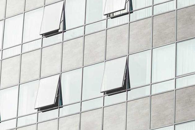 fachada comercial com pedra cinza simulando o modelo pele de vidro